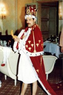 Freddie Mercury in his home wearing his crown with a banana.