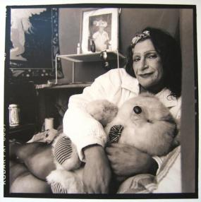 Sylvia Rivera posing in front of her altar to Marsha P. Johnson photo by Valerie Shaff, ca. 2000